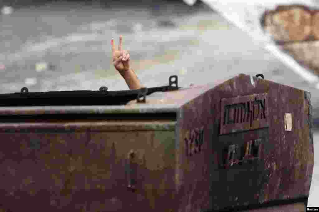A Palestinian protester gestures as he hides behind a metal container during clashes with Israeli security forces in east Jerusalem, Oct. 30, 2014.