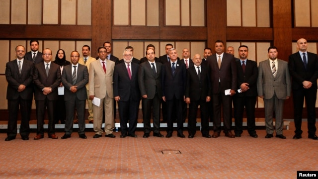 Libya's new Prime Minister Ahmed Maiteeq (6th L), President of the General National Congress Nouri Abusahmain (7th L) and other members of the new Libyan government pose for a group photo in Tripoli, May 26, 2014.