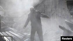26일 시리아 다마스쿠스 인근 구타의 반군 점령 지역인 메스라바에서 한 주민이 공습으로 무너지 건물을 살피고 있다.