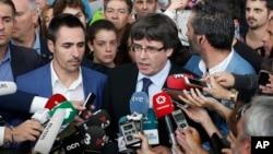 加泰罗尼亚自治区主席普伊格蒙特(中)在一个由体育场改成的投票点对媒体讲话。(2017年10月1日)