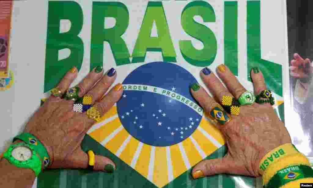 Marilza Guimarães da Silva, tem as unhas pintadas com as cores do Brasil e usa anéis alusivos à selecção. Não deve haver maior fã da equipa canarina. Brasília, Maio 27, 2014. REUTERS/Joedson Alves