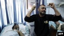 Một người Syria đứng bên cạnh người anh trai bị thương nặng trong một cuộc bạo lực giữa lực lượng an ninh và các nhóm vũ trang tại Syria