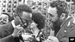 Fidel Castro montre à un leader du parti MPLA Agostinho Neto comment boire un daikiri, une boisson glacée cubaine, à La Havane, le 28 juillet 1976.