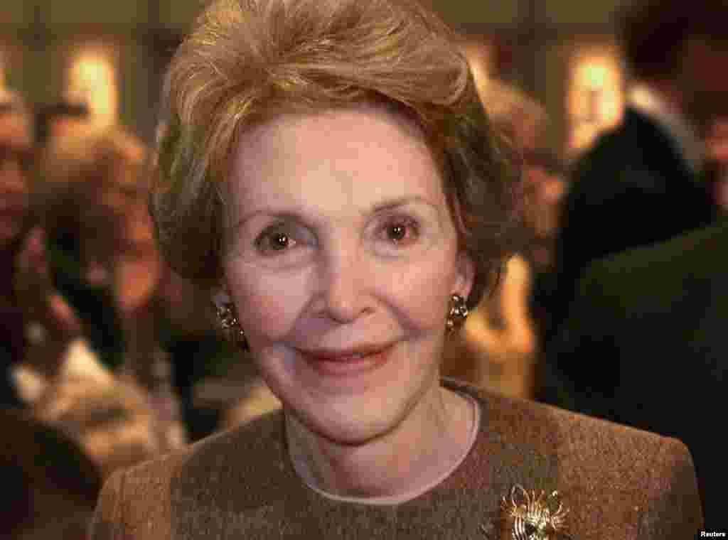 Former first lady Nancy Reagan smiles as she passes photographers after Texas Governor George W. Bush delivered his first major foreign policy speech at the Ronald Reagan Library in Simi Valley, California, Nov. 18, 1999.