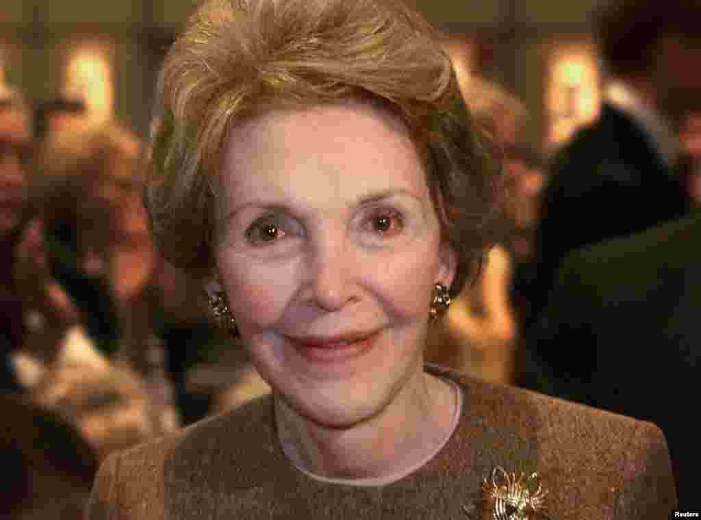 លោកស្រី Nancy Reagan អតីតភរិយាប្រធានាធិបតីអាមេរិក ញញឹមខណៈពេលដែលលោកស្រីដើរកាត់មុខអ្នកថតរូប បន្ទាប់ពីលោកអភិបាលរដ្ឋ Texas គឺលោក George W. Bush បានថ្លែងសុន្ទរកថាស្តីពីគោលនយោបាយបរទេសលើកទីមួយរបស់លោកនៅបណ្ណាល័យប្រធានាធិបតី Ronald Reagan នៅទីក្រុង Simi Valley រដ្ឋកាលីហ្វ័រញ៉ា កាលពីថ្ងៃទី១៨ ខែវិច្ឆិកា ឆ្នាំ១៩៩៩។