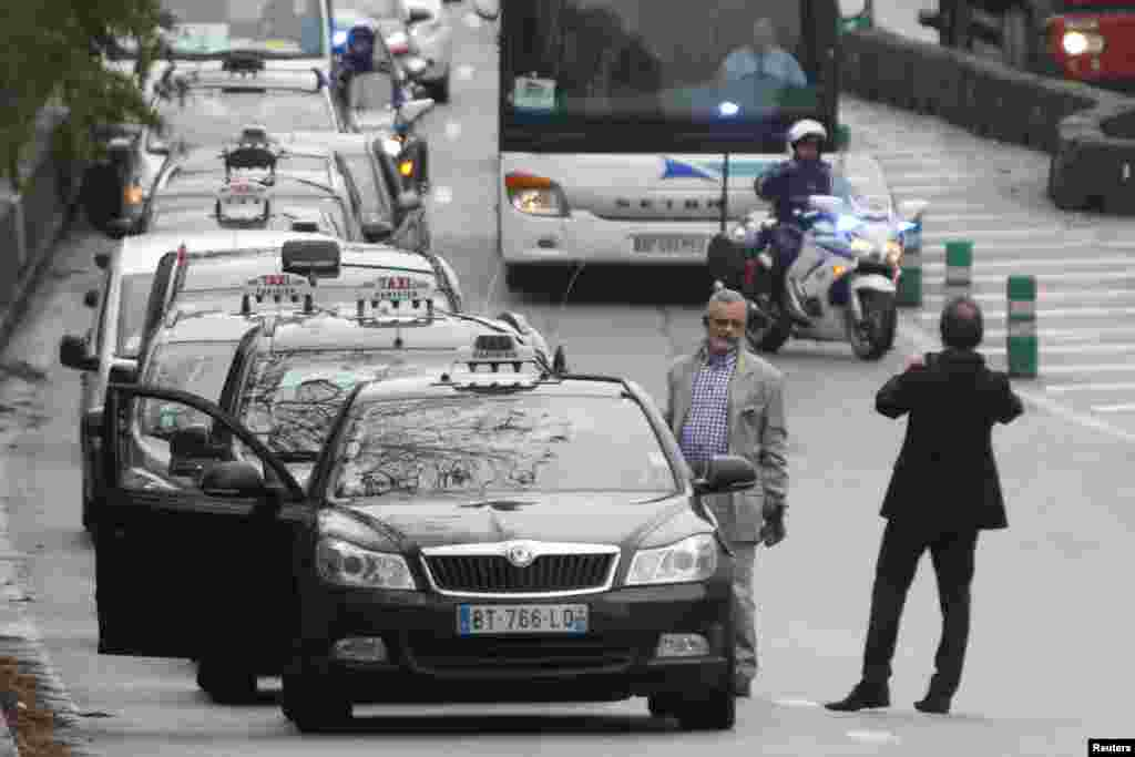 French motorcycle police escort striking Paris taxis which take part in a demonstration over the Paris ring road, Dec. 15, 2014.