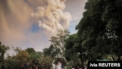 People attend a wedding ceremony as Taal Volcano sends out a column of ash in the background in Alfonso, Cavite, Philippines, January 12, 2020.