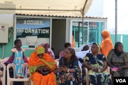 Women wait outside the Philippe Maguilen Senghor health center for free breast and cervical cancer screenings, in Yoff, Dakar, Senegal, April 22, 2017. (S. Christensen/VOA)
