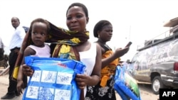 A woman carrying a baby holds a treated mosquito net during a malaria prevention action in Nigeria, April 21, 2016. WHO is providing anti-malaria drugs to children in northeast Nigeria in an effort to combat the disease.