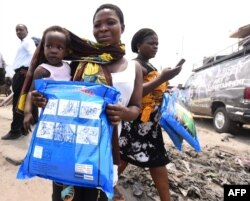 FILE - A woman carrying a baby holds a treated mosquito net during a malaria prevention action at Ajah in Eti Osa East district of Lagos, Nigeria, April 21, 2016.