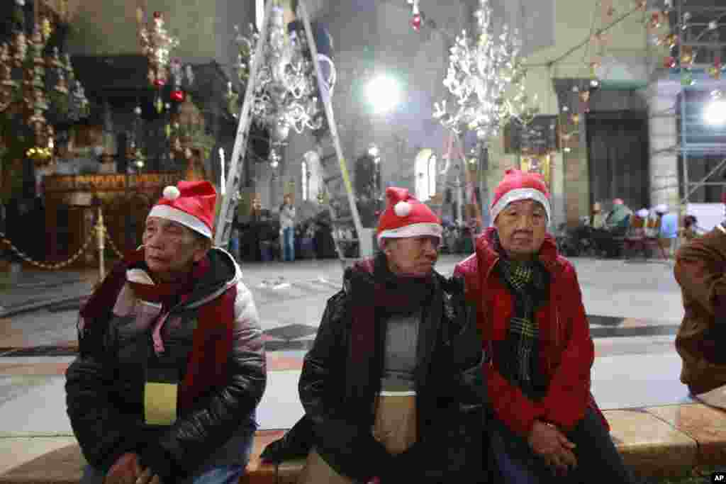 Christian worshippers visit the Church of the Nativity, traditionally believed by Christians to be the birthplace of Jesus Christ, in the West Bank town of Bethlehem on Christmas Eve, Dec. 24, 2013.
