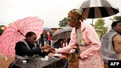 Một bà lão được đánh dấu trên ngón tay bằng mực không thể xoá trước khi bỏ phiếu ở Malawi, 20/5/2014.