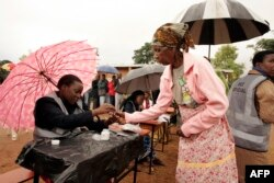 An old woman receives a mark on her finger with indelible ink prior to vote for Malawi's Tripartite elections at Malemia School Polling center, the home village of the incumbent president, May 20, 2014.