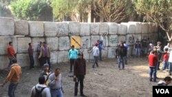 Para pengunjuk rasa Mesir berlindung di balik pagar buatan dari serangan militer Mesir di Kairo (19/12).