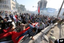 FILE - Protesters calling for government reforms run from tear gas fired by Iraqi security forces to disperse the crowd in central Baghdad, Iraq, May 27, 2016.