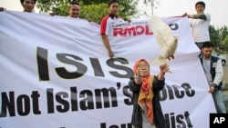 FILE - A Muslim woman releases a dove as a symbol of peace during a rally against the Islamic State group, in Jakarta, Indonesia.