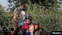 Des migrants syriens passent la frontière entre la Serbie et la Hongrie, en août 2015. (REUTERS/Bernardett Szabo)