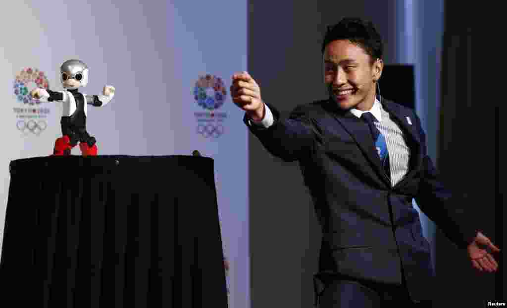 Japanese fencing Olympian Yuki Ota participates in a demonstration with talking robot Mirata during a news conference in support of the Tokyo 2020 summer Olympics candidacy in Buenos Aires, Argentina. The International Olympic Committee (IOC) will elect the host city for the 2020 summer Olympics at their session Sept. 7.