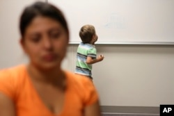 FILE - An unidentified immigrant from Guatemala is interviewed while her son paints on a whiteboard at the Artesia Family Residential Center, a federal detention facility, Sept. 10, 2014.