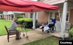 Trong mùa đại dịch, tháng bảy ở Mỹ không có mưa ngâu, nàng trên xe lăn, chàng vịn walker, Ngưu Lang Chức Nữ thời hiện đại, cả hai chỉ có 15 phút nhìn nhau bên ngoài cửa nursing home Ashbrook, New Jersey. [photo by Trần Qúi Thoại 2021]
