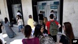 ປະຊາຊົນ ລຽນແຖວ ເພື່ອກົດເອົາເງິນ ອອກຈາກຕູ້ ATM ຢູ່ທະນາຄານແຫ່ງໜຶ່ງໃນເມືອງ Thessaloniki ທາງພາກເໜືອ ຂອງປະເທດ ກຣິສ, 27 ມິຖຸນາ 2015.