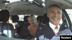 Norwegian Prime Minister Jens Stoltenberg and two passengers laugh, after they realize he was driving a taxi in Oslo, Aug. 11, 2013.