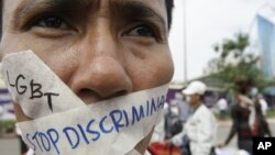 FILE PHOTO - A Cambodian protester tapes his mouth shut in protest against discrimination of the Lesbian, Gay, Bisexual and Transgender (LGBT), in front of National Assembly, in Phnom Penh, Cambodia, Friday, Nov. 16, 2012.