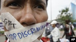 In this photo taken on Nov. 16, 2012, a Cambodian protester tapes his mouth shut in protest against discrimination of the Lesbian, Gay, Bisexual and Transgender (LGBT), in front of National Assembly, in Phnom Penh, Cambodia.