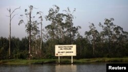 A warning sign belonging to the company Royal Dutch Shell is seen along the Nembe creek in Nigeria's oil state of Bayelsa Dec. 2, 2012.