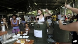 Evacuees who fled fighting in Ivory Coast prepare to eat breakfast in the French camp of Port Bouet, which houses about 3000 French and other foreign citizens, in Abidjan, April 8, 2011