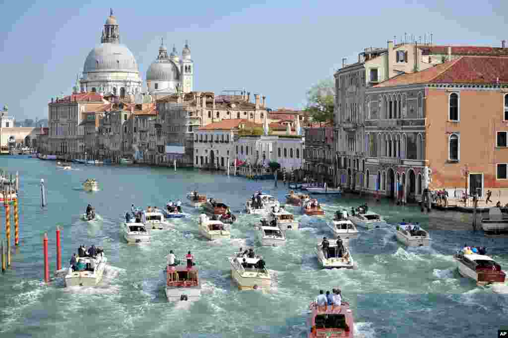 The boat carrying George Clooney and his wife Amal Alamuddin, is surrounded by media and security boats as they cruise the Grand Canal after leaving the Aman luxury Hotel in Venice, Italy.