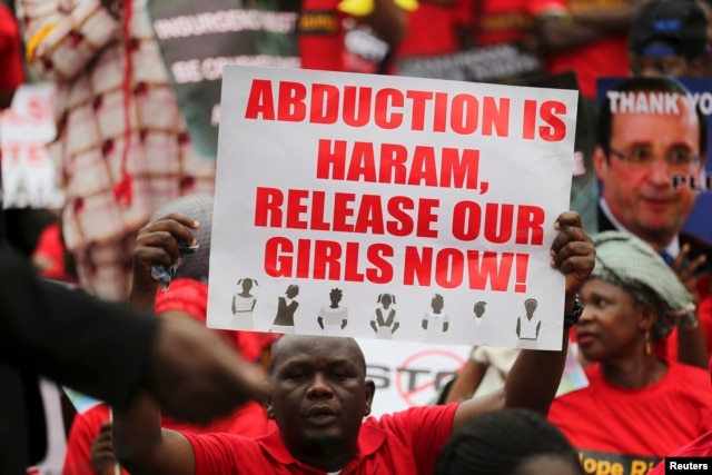 A man holds a placard calling for the release of secondary school girls abducted in the remote village of Chibok, during a protest along a road in Lagos, May 14, 2014.