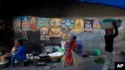 一名印度婦女1月2日打掃通道。後牆上貼有印度神像的海報。
