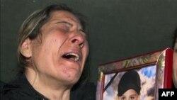 Bà Georgina Mtanious al-Jammal, cầm bức ảnh của con trai, cậu bé Sari Saoud, 9 tuổi bị bắn chết ở thị trấn Homs, Syria trong khi đang mua bánh trong một cửa hành