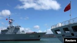 """参加2014环太平洋联合军演的中国海军""""千岛湖""""综合补给舰(左)驶过停泊在美国夏威夷军港里的中国海军医疗船""""和平方舟""""。(2014年6月24日)"""