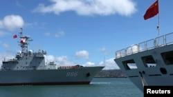 """參加2014環太平洋聯合軍演的中國海軍""""千島湖""""綜合補給艦(左)2014年6月24日駛過停泊在美國夏威夷軍港裡的中國海軍醫療船""""和平方舟""""。"""