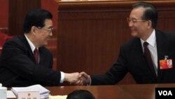 Perdana Menteri Tiongkok Wen Jiabao (kanan) berjabat tangan dengan Presiden Hu Jintao (Foto: dok). Cina akan melanjutkan program nuklirnya, setelah setahun bencana Fukushima, Jepang.