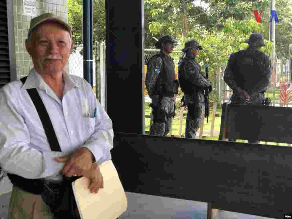 Un señor posa para la foto en la ciudad fronteriza de Pacaraima, Brasil, mientras militares custodian. Foto: Celia Mendoza - VOA.