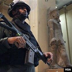 Seorang anggota pasukan keamanan menjaga sebuah museum di Kairo. PBB mengecam penggunaan kekerasan terhadap para demonstran.