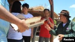 Blaine Gibson, seorang pengacara asal AS yang berubah menjadi penyelidik swadana (kanan) dan anggota keluarga dari beberapa penumpang menguji reruntuhan yang diduga berasal dari Malaysia Airlines nomor penerbangan MH370, yang membawa 239 penumpang dan awak, yang hilang lebih dari dua tahun yang lalu (foto: REUTERS/Clarel Faniry Rasoanaivo)