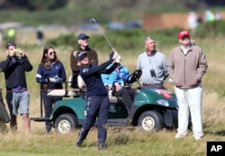 Donald Trump, right, then a presidential candidate, watches England's Charley Hull play her shot on the 16th fairway on the first day of the Women's British Open golf championship on the Turnberry golf course in Scotland, July 30, 2015.