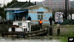 Authorities check the dead pigs, not seen, which have been pulled out from the river on a barge, Mar. 11, 2013, on the outskirts of Shanghai, China.