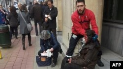 FILE - A private security guard helps a wounded woman outside the Maalbeek metro station in Brussels after a blast there March 22, 2016. The prime minister acknowledged security lapses but defended anti-terror efforts.