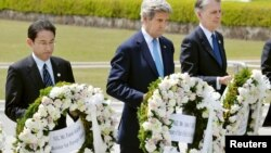 U.S. Secretary of State John Kerry (center) prepares to lay a wreath with Japan's Foreign Minister Fumio Kishida (L), Britain's Foreign Minister Philip Hammond at Hiroshima Peace Memorial Park during the G-7 ministers' meeting.