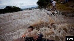 El salvadoreño Edwin Enríquez intenta cruzar junto con su familia a territorio seguro luego de que el puente internacional que divide El Salvador con Guatemala colapsara por las lluvias.