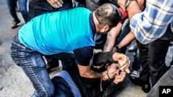 Polisi Turki menahan seorang demonstran anti KTT G-20 di Antalya, Turki (15/11).