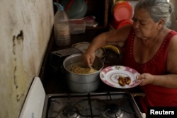 Antonia Torres, mother of Yuni Perez, cooks for seven people a packet of pasta received in a CLAP box, a Venezuelan government handout of basic food supplies, in her home at the slum of Petare in Caracas, March 9, 2018.