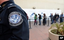 FILE - In this Dec. 10, 2015, file photo, pedestrians crossing from Mexico into the United States at the Otay Mesa Port of Entry wait in line in San Diego.