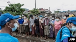 Na ovoj fotografiji snimljenoj 21. maja 2021. godine ljudi čekaju da dobiju vrećice riže koju je dijeli Svjetski program za hranu (WFP) u sklopu napora pomoći u hrani za podršku stanovnicima koji žive u siromašnim zajednicama na periferiji Yangona.