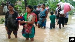 Nepalese villagers carry their belongings while wading through a flooded street to move to safer ground, at Bardia, in western Nepal.